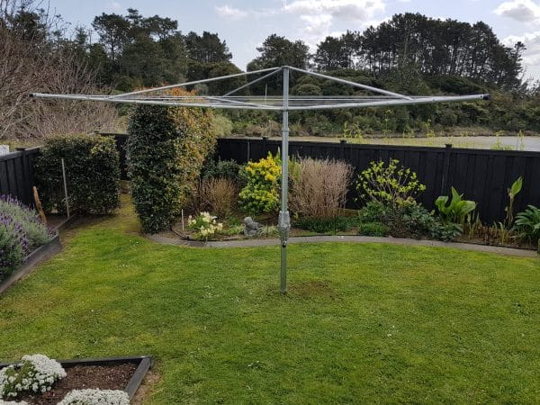 A fixed head hoist clothesline set in the lawn of a back garden surrounded by plants.
