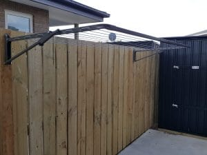 Austral Compact fold down washing line attached to a wooden fence with wooden supports over a concrete pad