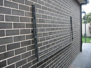 Austral Compac 39 fold down washing line folded down against the brick wall of a house which it is fixed to