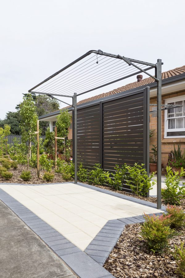 Austral Compact fold down washing line attached to a leg frame kit in a garden with a paved area in front and a screened fence behind