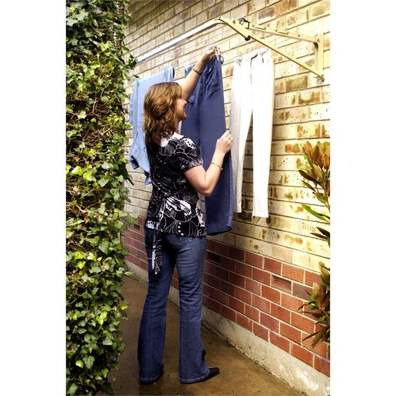 Woman hanging clothes on an Austral Slenderline fold down clothesline attached to a brick house wall
