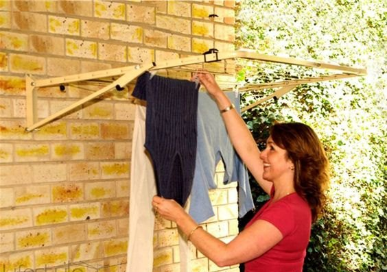 Woman hanging clothes on an Austral Unit fold down washing line attached to a brick wall