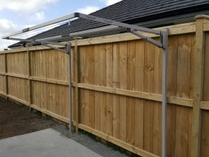 Hills Double Folding Frame clothesline attached to metal legs located in front of a wooden fence in a garden with a concrete pad in front