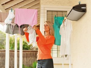 Woman hanging clothes in a covered outside area on a Hills Extendaline retractable washing line attached to the wall