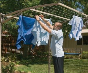 Man hanging shirts to dry on a folding frame washing line mounted on a metal frame in a garden