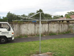 A metal rotary washing line in a garden with a truck from Auckland Clotheslines to one side
