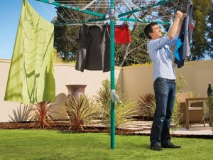 A man hanging washing outdoorson a Hills Rotary 6 clothesline in a sunny garden