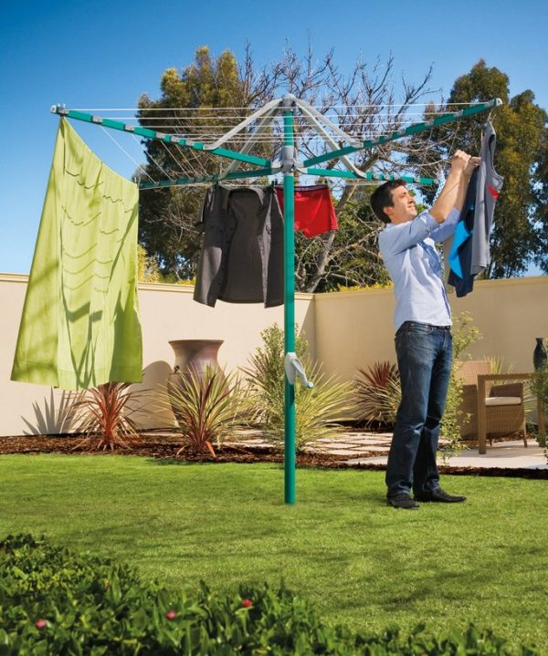 A man hanging washing on a Hills Rotary 6 clothesline in a sunny garden