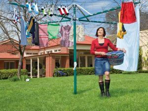 A woman carrying a washing basket to hang washing on a Hills Rotary 7 washing line in the garden