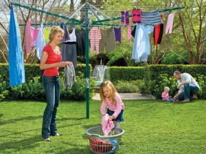 A family hanging out washing in a garden on a rotary washing line