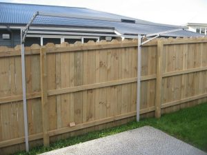 A single folding frame washing line on a metal frame mounting kit located in a garden in front of a wooden fence
