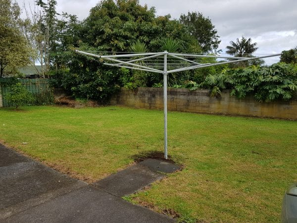 Tasman Galvanised Rotary washing line at the end of a concrete path in a garden