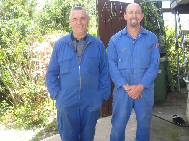 Two men who work for Auckland Clotheslines dressed in blue overalls and smiling