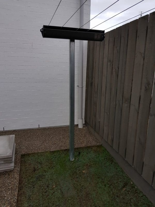 End on view of an Austral Retractaway retractable clothesline set on a post in a grassed area