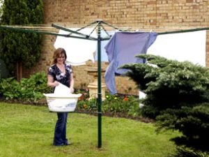 Woman getting washing out of a basket to hang on an Austral Foldaway 45 clothesline