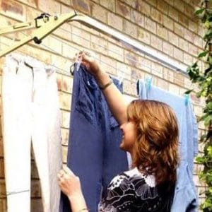 Woman hanging washing on the Austral Slenderline 16 Fold Down Clothesline