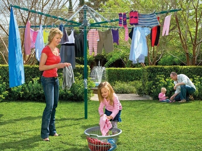 Family hanging out the washing, small girl helping hand washing to her mother