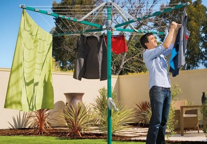 Man hanging washing on a Hills Rotary 6 folding head hoist clothesline set in a back garden